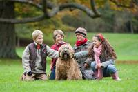 Four children in park, crouching, stroking dog