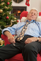 Senior man holding champagne flute asleep in armchair at christmas