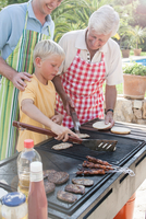 Boy cooking kebabs and burgers on barbecue with father and grandfather