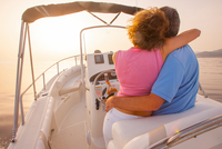 Romantic mature couple driving speedboat at sunset, Majorca, Spain