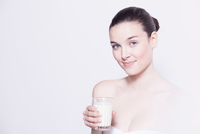 Portrait of beautiful young woman holding glass of milk