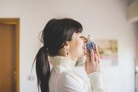Young woman holding pet bird indoors 11015276100  写真素材・ストックフォト・画像・イラスト素材 アマナイメージズ