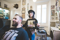 Female barber holding up mirror behind man in shop