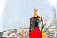 Portrait of young businesswoman, standing outside modern office building, smiling 11015276433| 写真素材・ストックフォト・画像・イラスト素材|アマナイメージズ