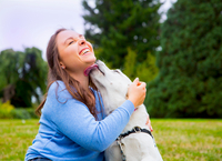 Young woman sitting with dog in park, dog licking woman's face