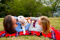 Two young women with pet dog, lying on blanket in park