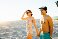 Young couple wearing swimming costume and shorts strolling on beach, Venice Beach, California, USA