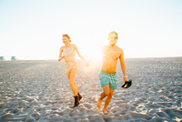 Young couple wearing swimming costume and shorts running on sunlit beach, Venice Beach, California, USA