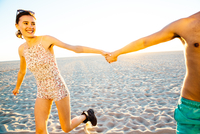 Young couple wearing swimming costume and shorts holding hands on beach, Venice Beach, California, USA