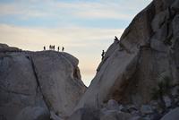 Hikers climbing rock, Mojave Desert, Joshua Tree National Park, California