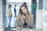 Young businesswoman sitting at desk, using telephone, smiling