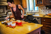 Woman preparing snacks at kitchen counter watched by pet dog