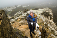 Portrait of female hiker with her dog holding snowball in misty mountains, Spain