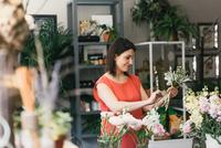 Florist arranging bouquet in flower shop, smiling
