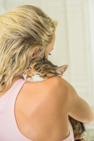 Rear view of woman cuddling cat