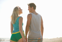 Rear view of couple on beach face to face smiling