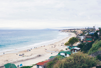 Elevated view of beach huts and distant tourists on beach, Crystal Cove State Park, Laguna Beach, California, USA