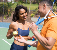 Couple chatting on tennis court