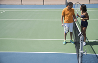 Couple chatting beside tennis court net