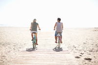 Rear view of couple cycling on boardwalk at Venice Beach, Los Angeles, California, USA