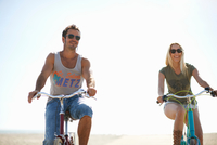 Cycling couple cycling on Venice Beach, Los Angeles, California, USA