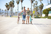 Cycling couple strolling with cycles at Venice Beach, Los Angeles, California, USA