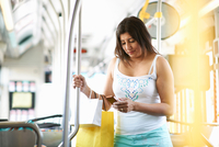 Woman standing on bus with shopping reading smartphone texts, Los Angeles, California, USA