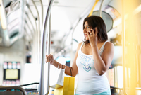 Woman standing on bus chatting on smartphone, Los Angeles, California, USA