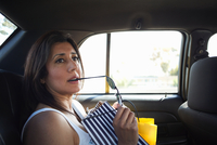Woman sitting with shopping bags in back seat of taxi, Los Angeles, California, USA