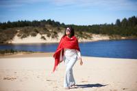 Woman in red shawl enjoying beach