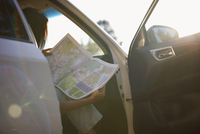 Woman reading map inside vehicle
