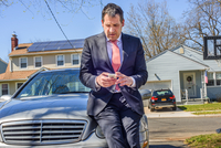 Business man leaning against car using smartphone