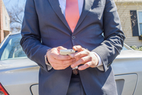 Cropped view of business man leaning against car using smartphone