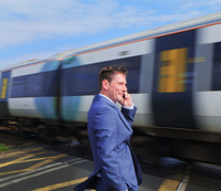 Businessman standing at level crossing, using smartphone