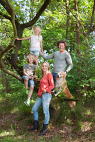 Family in forest climbing tree looking at camera smiling