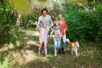 Family with dog walking together in forest