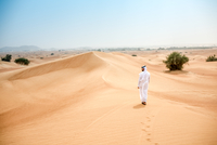Rear view of young middle eastern man wearing traditional clothes walking in desert, Dubai, United Arab Emirates