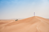 Young middle eastern man wearing traditional clothes looking out from desert dune, Dubai, United Arab Emirates