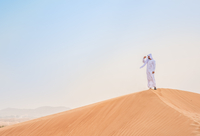 Middle eastern man wearing traditional clothes looking out from desert dune, Dubai, United Arab Emirates