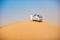 Middle eastern man wearing traditional clothes with off road vehicle parked on desert dune, Dubai, United Arab Emirates