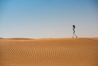 Woman tourist walking on desert dune, Dubai, United Arab Emirates