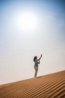 Woman tourist taking smartphone selfie on desert dune, Dubai, United Arab Emirates