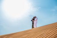 Middle eastern couple wearing traditional clothes taking smartphone selfie on desert dune, Dubai, United Arab Emirates
