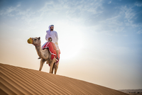 Man wearing traditional middle eastern clothes riding camel in desert, Dubai, United Arab Emirates