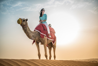 Female tourist riding camel in desert, Dubai, United Arab Emirates