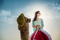Low angle view of female tourist riding camel in desert, Dubai, United Arab Emirates