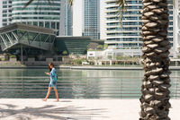 Female tourist strolling along waterfront reading smartphone texts, Dubai, United Arab Emirates