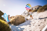 Girl and brother running down sand dune carrying shark inflatable and beachball, Cape Town, South Africa