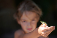 Portrait of boy holding up frog on hand, Buonconvento, Tuscany, Italy