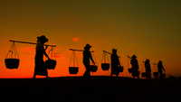 Silhouette of workers carrying yoke and buckets at sunset, Myanmar